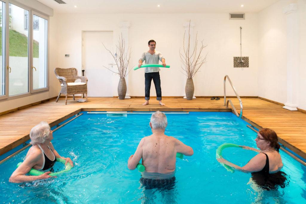 Des résidents font de l'aquagym à l'aide d'un professeur, notre réponse à la question : Comment fonctionne une résidence senior ?
