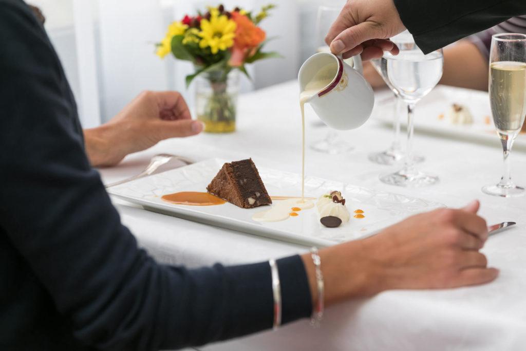 Serveur versant un coulis sur un dessert au sein du restaurant Villa Médicis